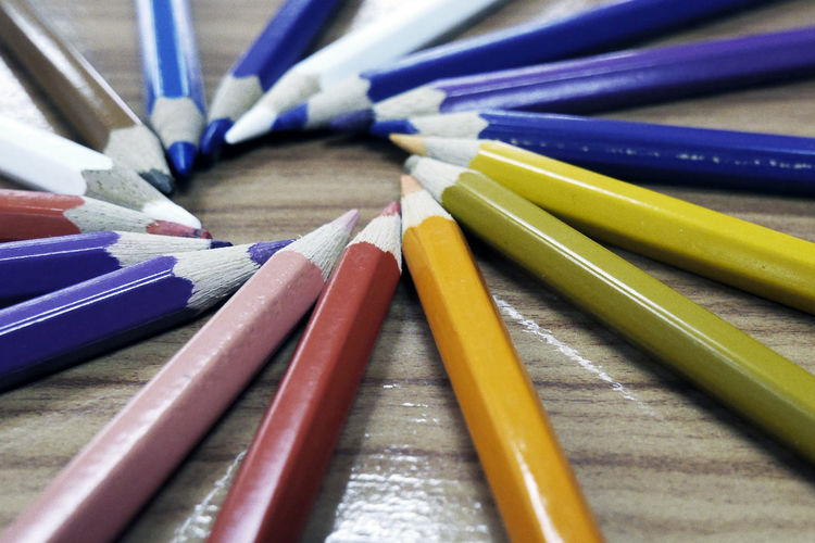 Close-Up Of Multi Colored Pencils Arranged On Wooden Table