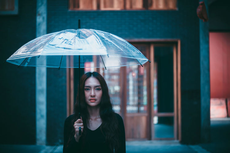 Portrait of woman with umbrella standing in city