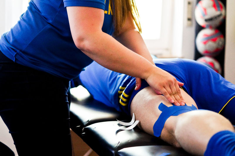 Midsection Of Woman Applying Bandage On Sport Player Thigh