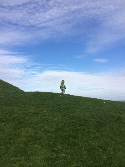 Low Angle View Of Girl Standing On Grassy Field Against Sky