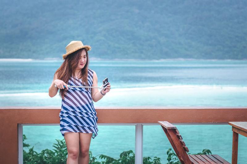 Woman adjusting mobile phone in monopod against sea