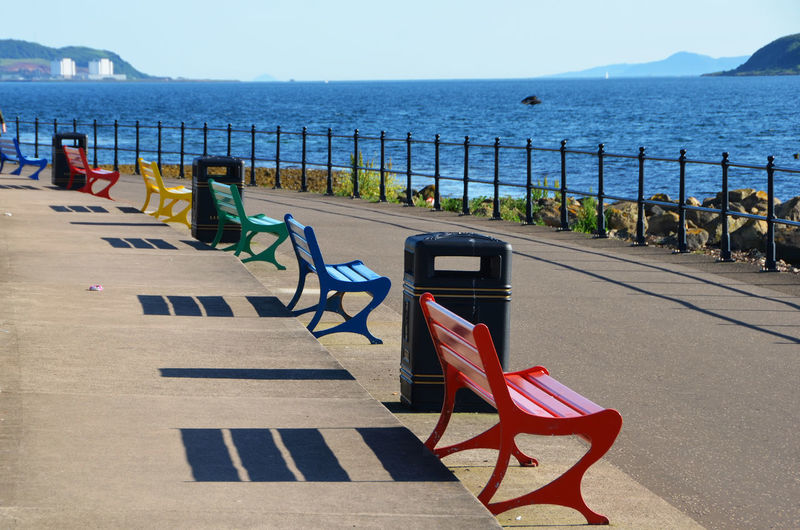 Colorful benches on footpath by sea