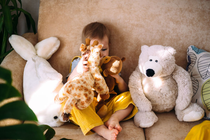 Funny little child is having fun, playing with soft toys on the couch at home.