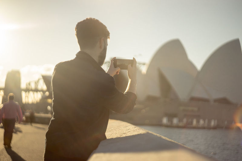 Rear view of man photographing through mobile phone in city