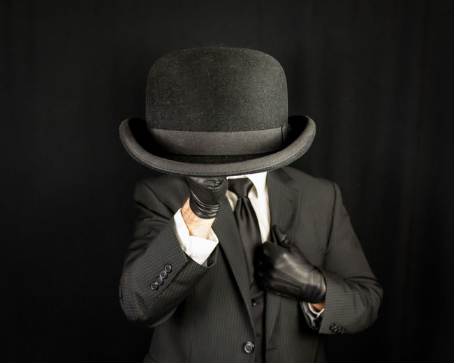 Midsection of man holding hat against black background