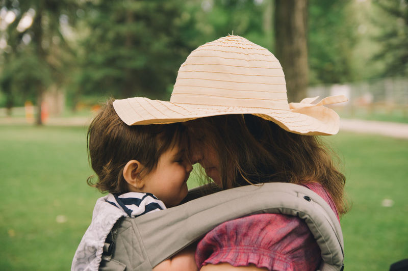 Mommy and baby boy having a cuddle in the park. Baby Boy Casual Clothing Childhood Day Family Garden Hanging Out Happy Hat Headshot Leisure Activity Lifestyles Long Hair Love Mother And Son Nature Outdoors Park Tree