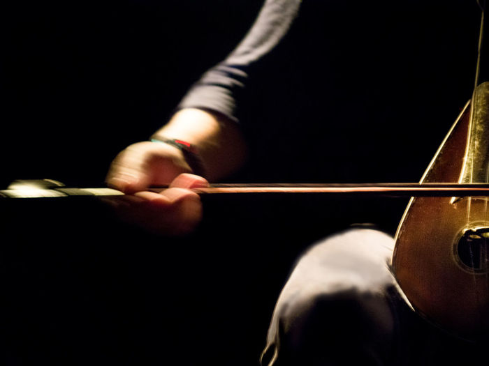 Midsection of man playing string instrument against black background