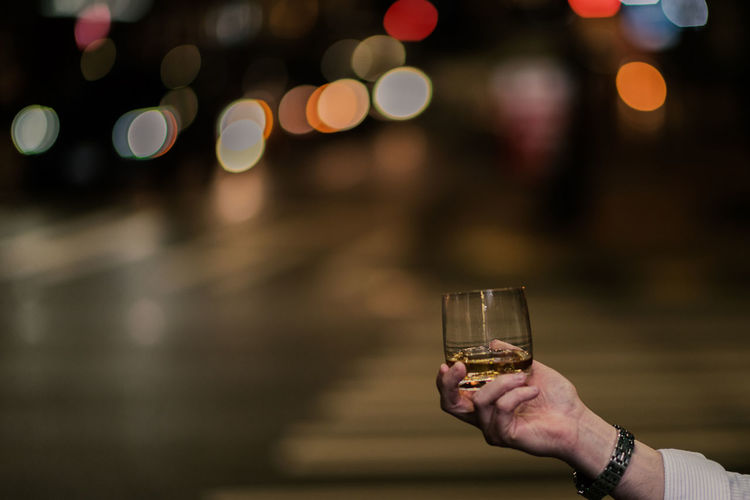 Close-up of hand holding alcohol glass on street at night