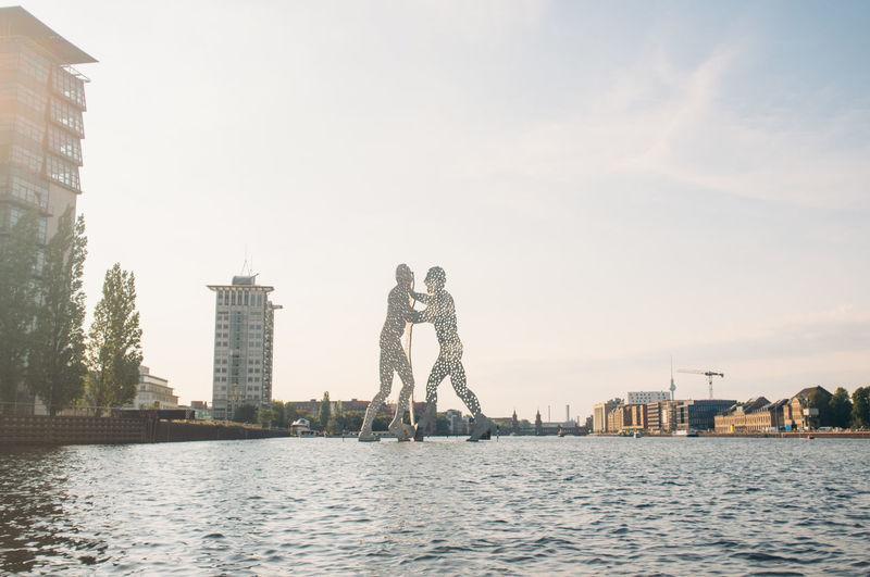 Molecule man sculpture on spree river against sky