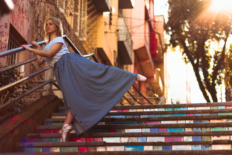 Woman dancing on steps in city
