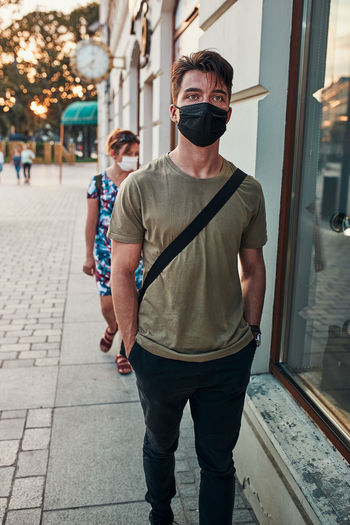 Young man walking along a store front in the city center in the evening wearing the face mask