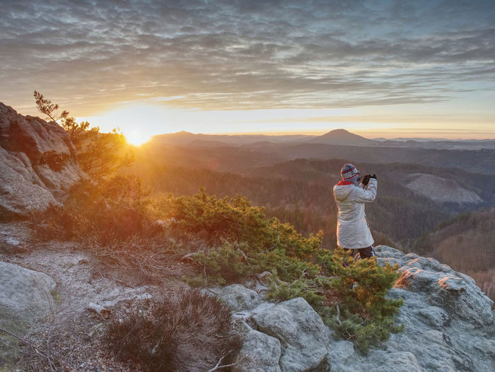 Photograper with hand on camera and tripod. woman climbed up on exposed rock for fall photos