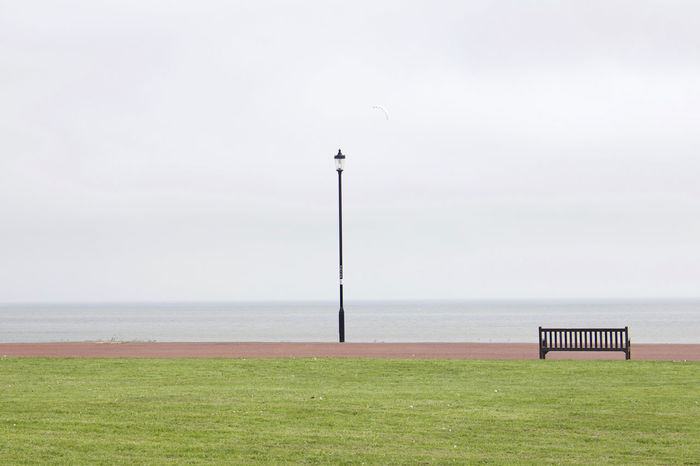 Safe in Simplicity. Beauty In Nature Bench Day EyeEmAwards17 EyeEmNewHere Grass Lamppost Minimalism Minimalist Minimalist Photography  Minimalobsession Nature No People Outdoors Promenade Scenics Sea Sea And Sky Seaside Sky Tranquil Scene Tranquility Water