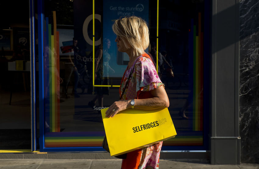A woman carrying Selfridges yellow shopping bag in Regent Street on 9th of July 2018 in London, United Kingdom. Regent Street is one of Londons most popular destinations and is home to a wide variety of shops, from iconic department store Selfridges to top British heritage brands. (photo by Lorenzo Grifantini) Oxford Circus Selfridges Females Hairstyle Leisure Activity Lifestyles Retail  Shop Store Women Yellow
