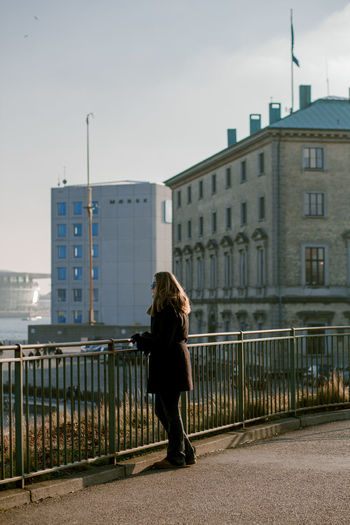 Woman standing by railing against buildings in city