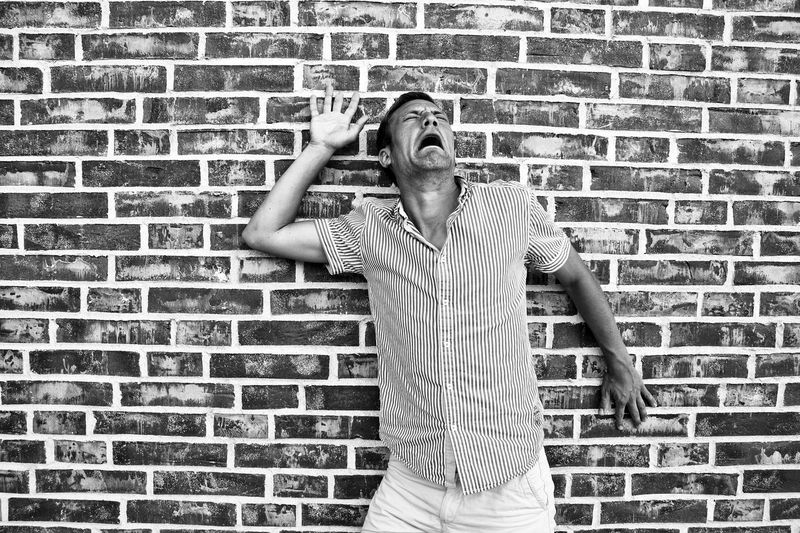 Man making face while standing against brick wall