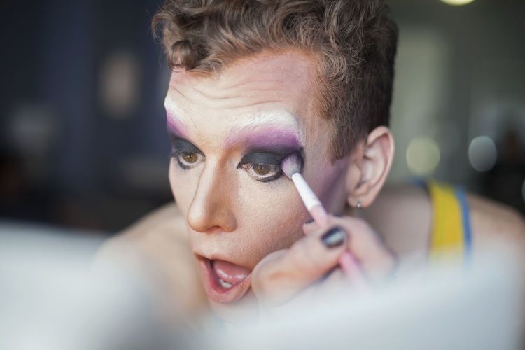 Young man applying drag queen makeup