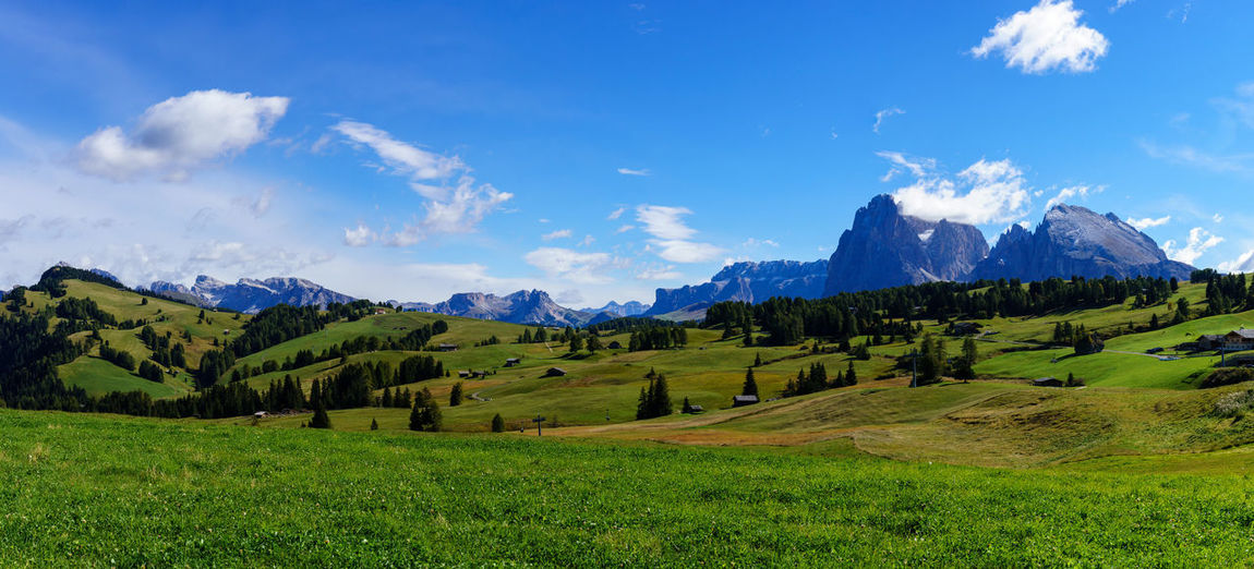Panoramic view of green landscape and mountains against blue sky