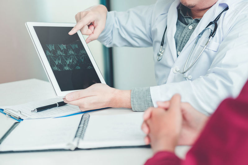 Midsection of doctor showing x ray in digital tablet to patient at desk in hospital