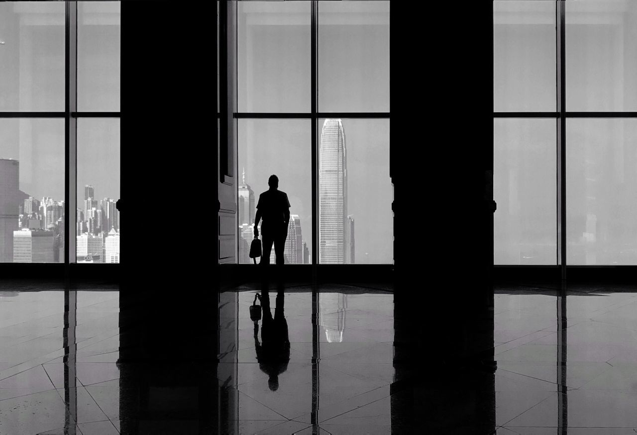 Silhouette man looking at international finance centre through window