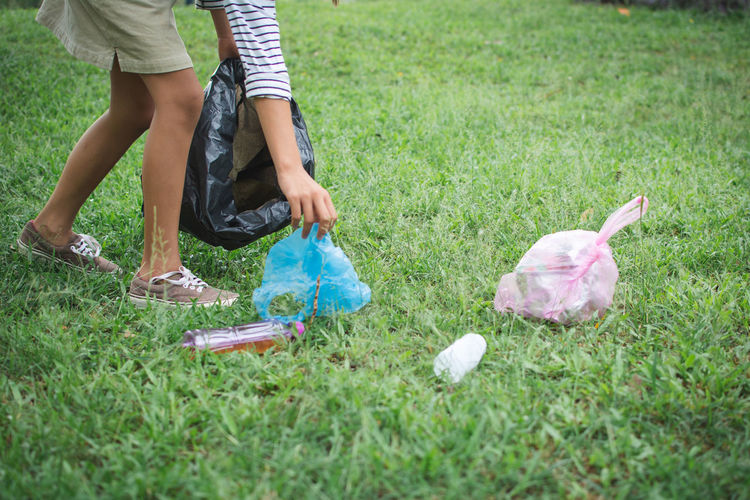 Close-Up Of Woman Collecting Garbage On Grass Field