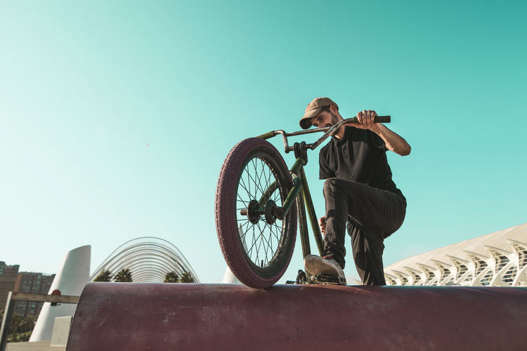 Low angle view of man cycling against sky