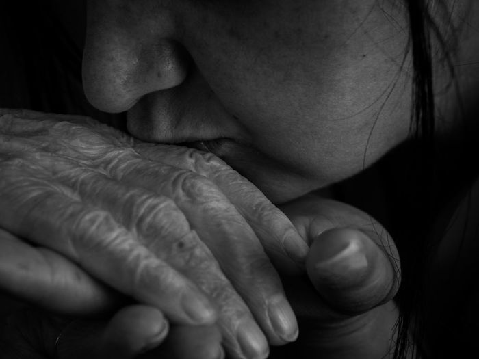Cropped image of woman kissing parent hand