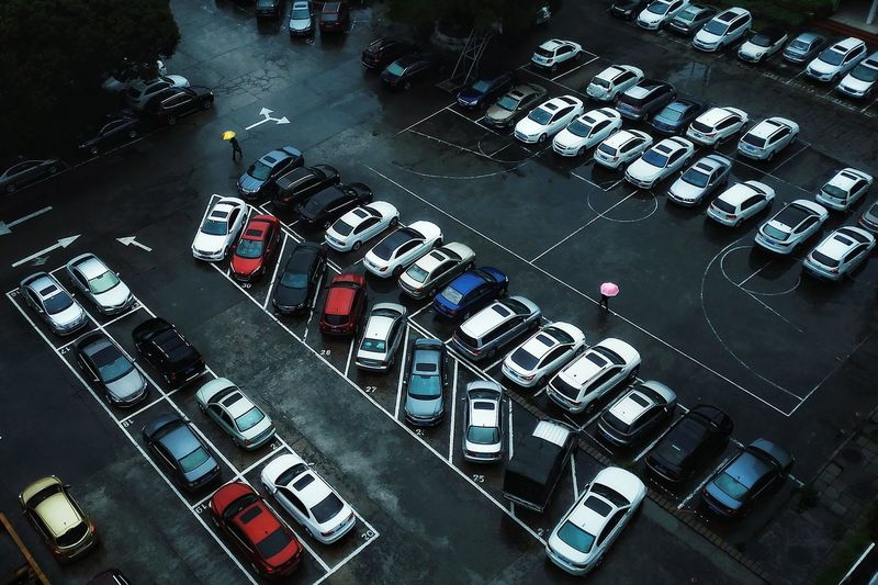 High angle view of cars parked at parking lot in rain