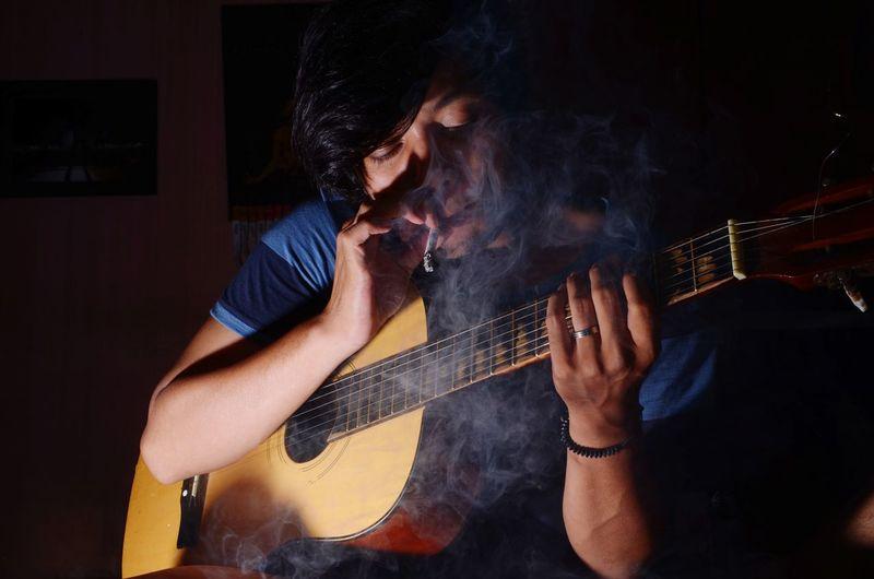Man smoking cigarette while playing guitar in darkroom