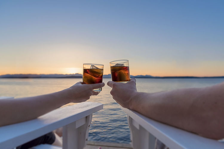Cropped image of hands toasting against sea during sunset