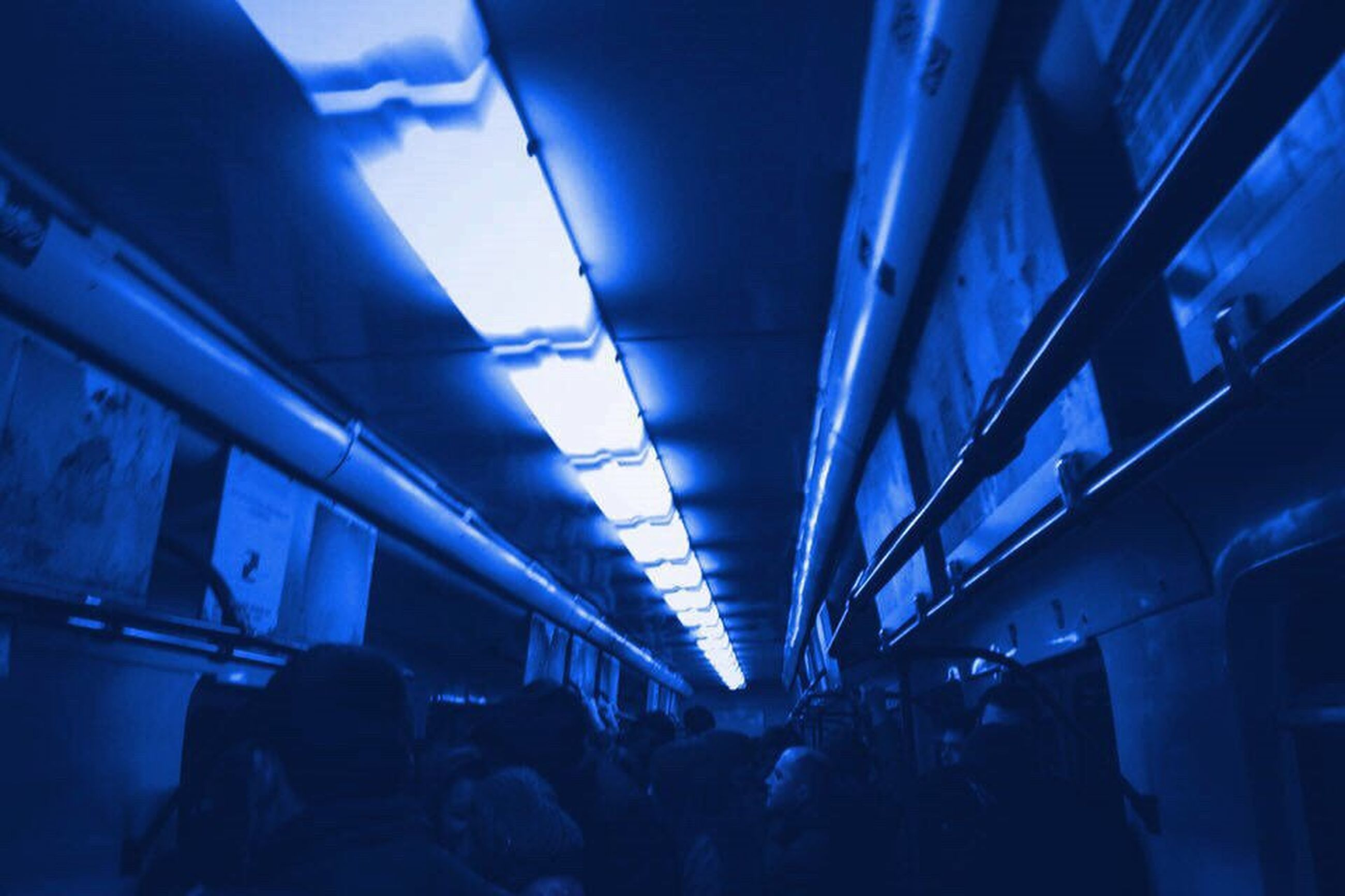 illuminated, indoors, lighting equipment, blue, transportation, travel, lifestyles, subway station, large group of people, mode of transport, real people, men, people, neon, public transportation, subway train, night, commuter, rush hour, crowd, adults only, adult