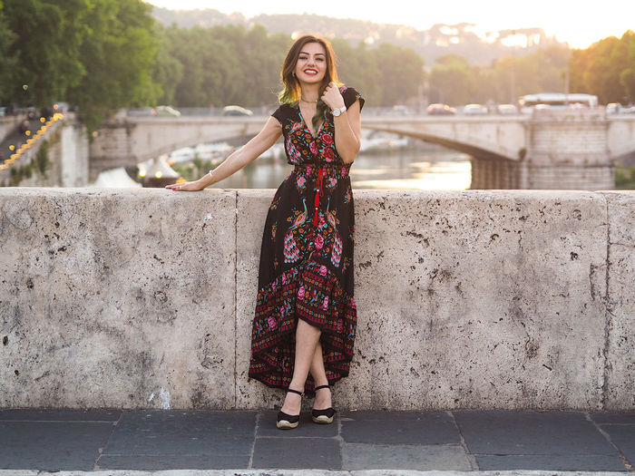 Portrait of beautiful woman leaning on railing while standing on footpath