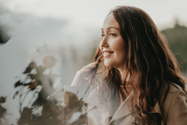 Smiling woman looking away seen through window