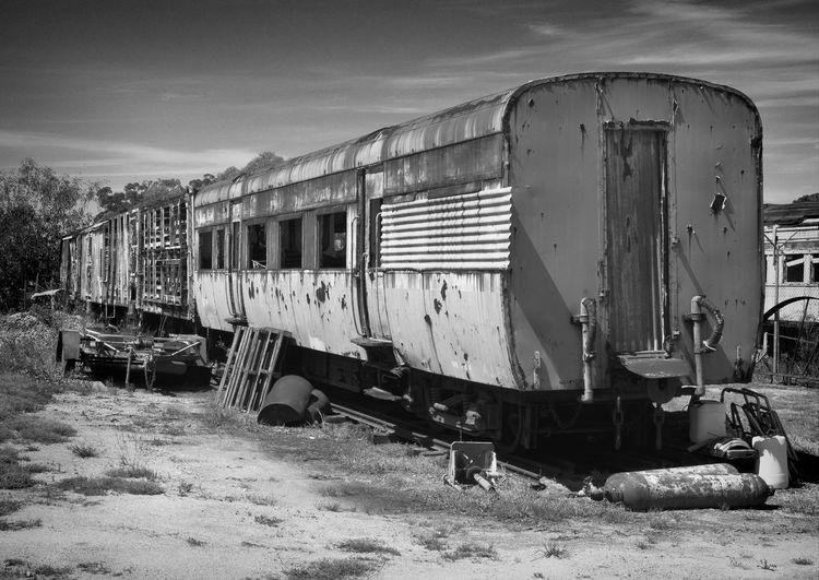 Abandoned train on land against sky