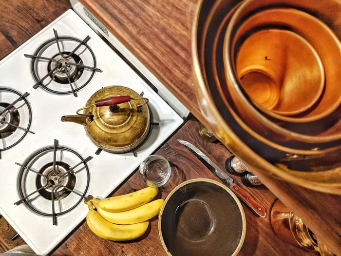 Surrealistic close-up of kitchen life in a tiny house. Kitchen Banana Teapot Copper  Wood Stove Surrealism High Angle View Tiny House  High Angle View Close-up Directly Above Served Kettle Kitchen Counter Afternoon Tea Tea Kettle Creative Space The Still Life Photographer - 2018 EyeEm Awards