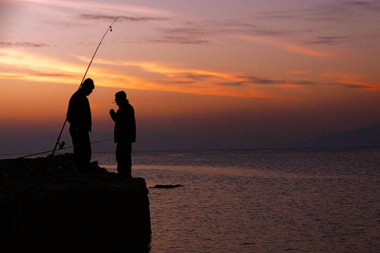 Silhouette men fishing in sea during sunset