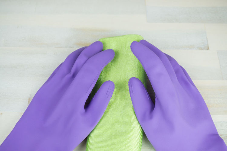 Cleaning Household Housekeeping Housework Hygiene Blue Cleaning Rag Close-up Day Fabric Glove Housecleaning Human Body Part Human Hand Indoors  Low Section Multi Colored One Person People Rag Real People Rubber Gloves Spring Cleaning Stuff Wooden Background