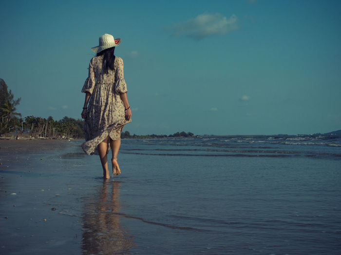 Women who wear vintage dresses are walking on the beach with excitement to relax. This summer, let's go to the sea. Water Real People Full Length One Person Sea Lifestyles Leisure Activity Clothing Sky Beauty In Nature Hat Beach Land Vacations Walking Day Nature Trip Rear View Outdoors