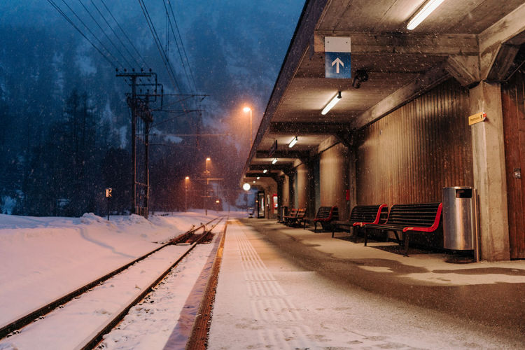 Empty train station in Suiss mountains during snow fall Transportation Snow Cold Temperature Rail Transportation Illuminated Winter Railroad Track Architecture Lighting Equipment Track Mode Of Transportation No People Street Night Nature Built Structure Building Exterior The Way Forward Street Light Snowing Outdoors Electricity  Light Electric Lamp