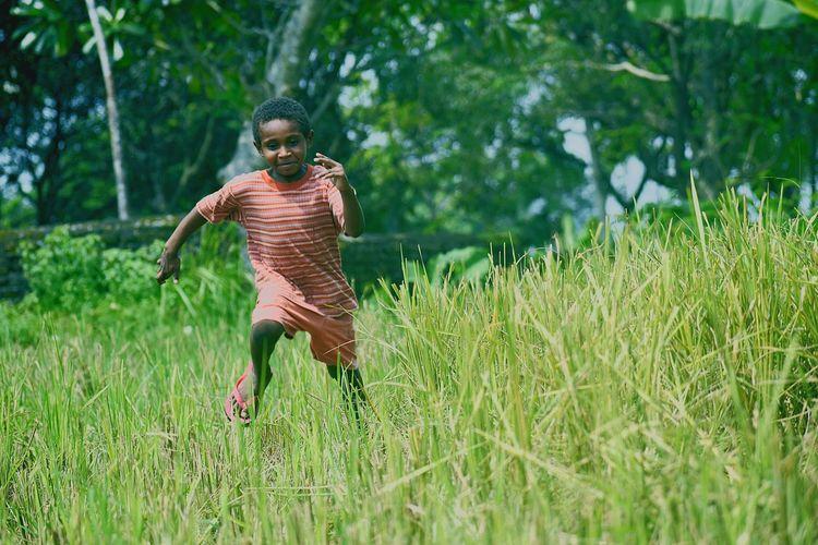 Full length of a man running on grass