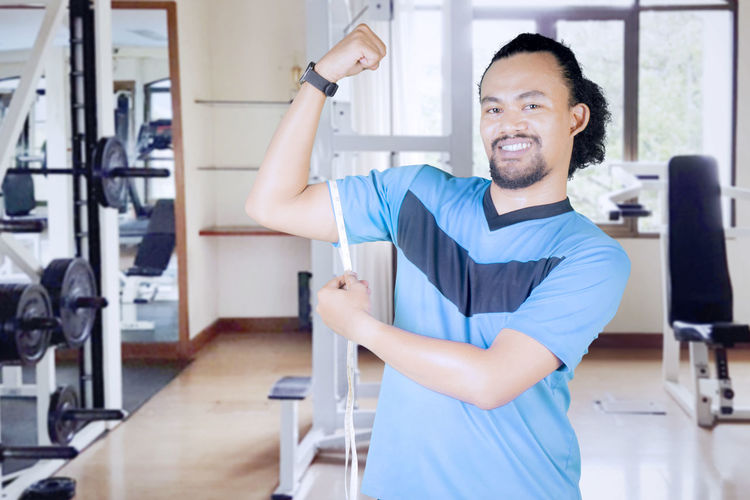 Portrait of smiling young man measuring arm in gym