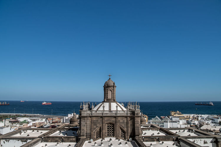 Panoramic view of sea and buildings against clear blue sky