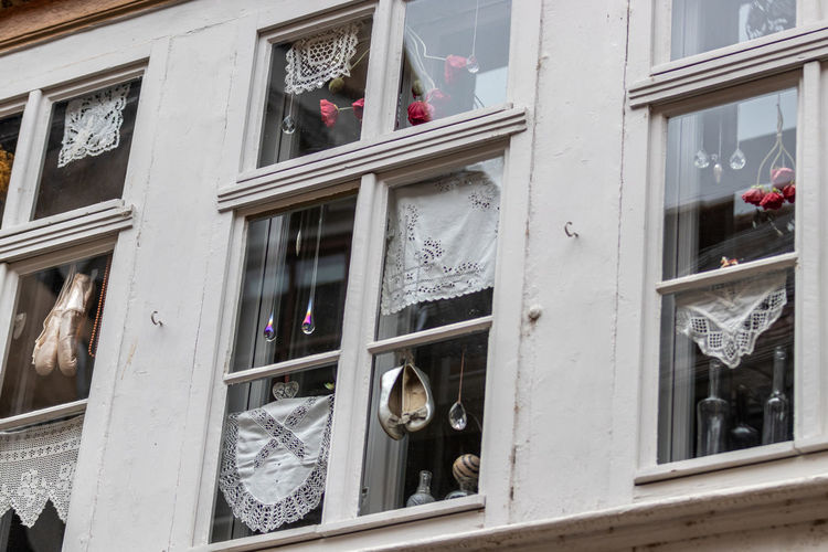 Low angle view of window hanging on building