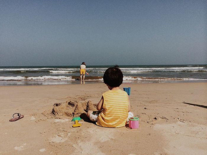 Rear view of two kids on beach
