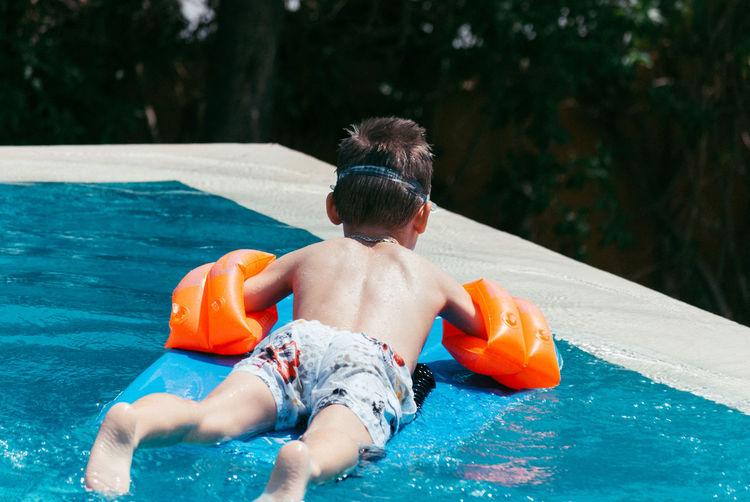 Rear View Of Shirtless Boy In Swimming Pool