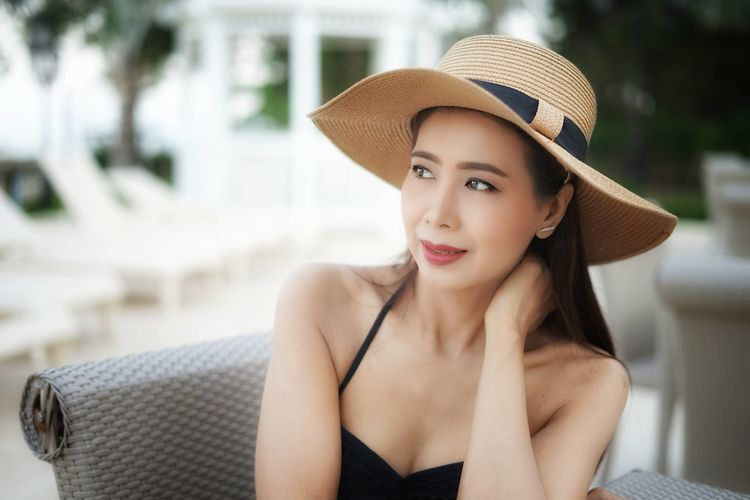 Beautiful young woman looking away while wearing hat