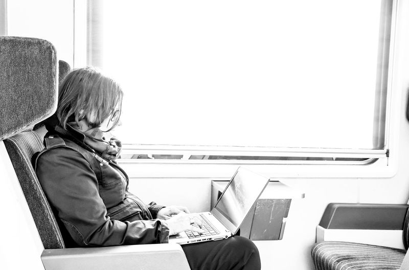 Business Woman Working on Laptop in First Class in a Train in Switzerland. Sitting Wireless Technology Technology Connection Window Communication Indoors  Computer One Person Real People Laptop Side View Seat Using Laptop Train - Vehicle Rail Transportation Transportation Working Black And White Commuter Business Businesswoman Travel Modern Lifestyle