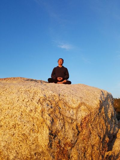 Low angle view of man meditating on rock against clear sky