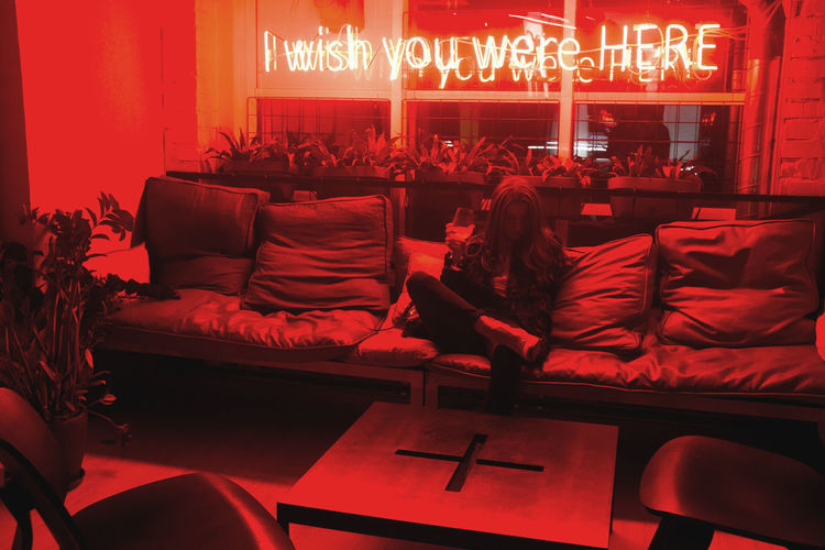 EyeEmNewHere Focus On The Story WeekOnEyeEm Adult Adventures In The City Business Communication Furniture Group Of People Illuminated Indoors  Lighting Equipment neon life Night People Real People Red Relaxation Seat Sign Sitting Sofa Text Western Script Women