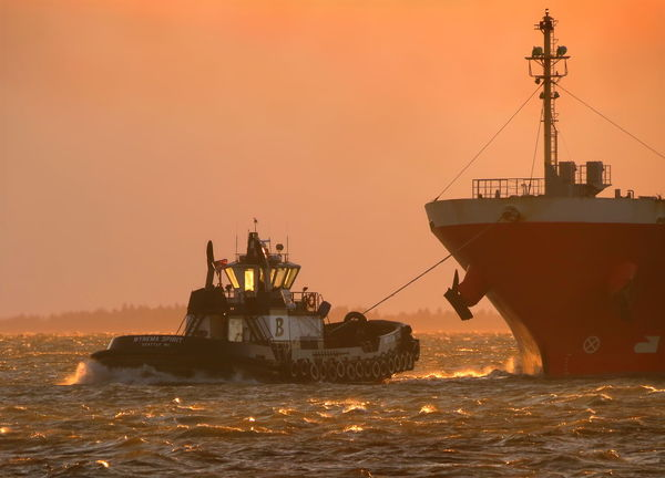 Powerful tug boat wresting a massive cargo ship against fierce waves, tide, and currents to bring her safely into port. Boat Cargo Container Ship Currents Golden Grays Harbor Maritime Nautical Orange Pink Port Red Sea Ship Shipping  Storm Sunset Tide Transportation Tug Vessel Water Waves Weather